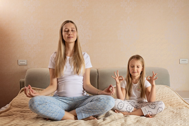 Pregnant woman and her daughter sitting in lotus position while meditating