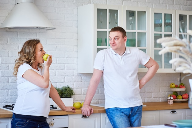 Pregnant woman and her husband in the kitchen at home with fruit.