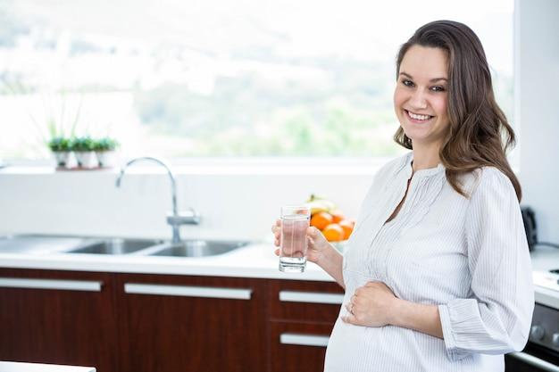 妊娠中の女性が台所で水の入ったグラスを保持