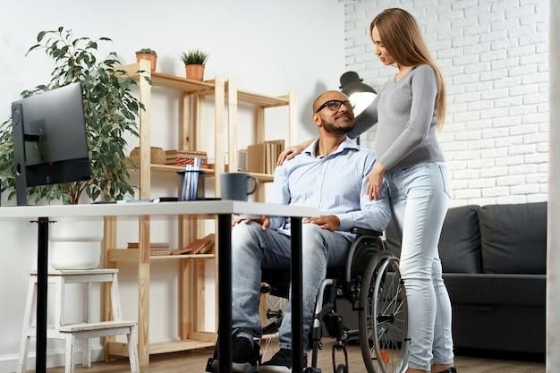 Беременная женщина, держащая за руку своего мужа-инвалида, сидящего в инвалидной коляске