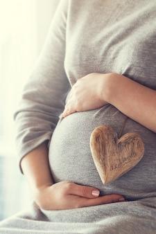 임신 한 여자는 그녀의 아랫 배를 만지고있는 동안 마음을 잡고
