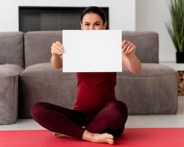 흰색 카드를 들고 임신 한 여자