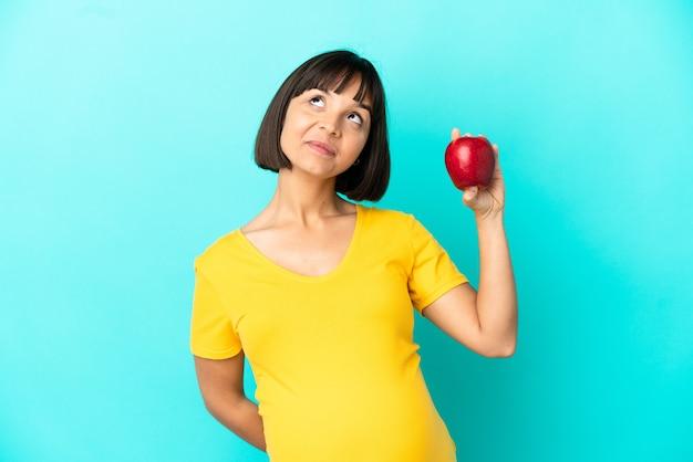 Беременная женщина держит яблоко на синем фоне и смотрит вверх
