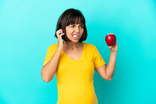 Беременная женщина, держащая яблоко, изолированное на синем фоне, разочарована и закрывает уши