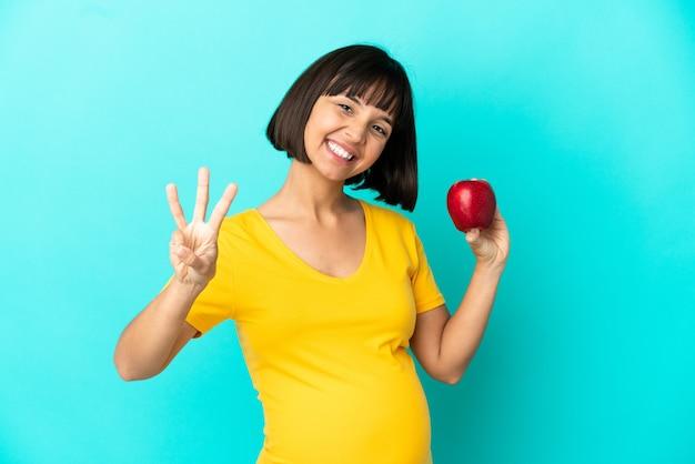 Беременная женщина, держащая яблоко, изолированное на синем фоне, счастлива и считает три пальцами