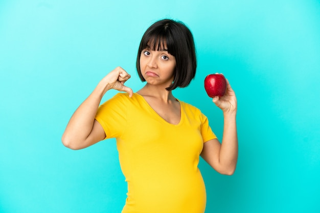 Беременная женщина, держащая яблоко на синем фоне, гордая и самодовольная