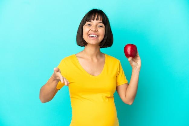 Беременная женщина, держащая яблоко на синем фоне, пожимая руку для заключения хорошей сделки