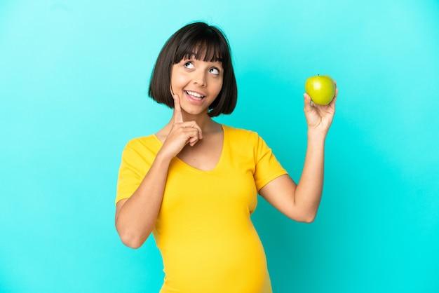 Беременная женщина, держащая яблоко, изолированное на синем фоне, думает об идее, глядя вверх