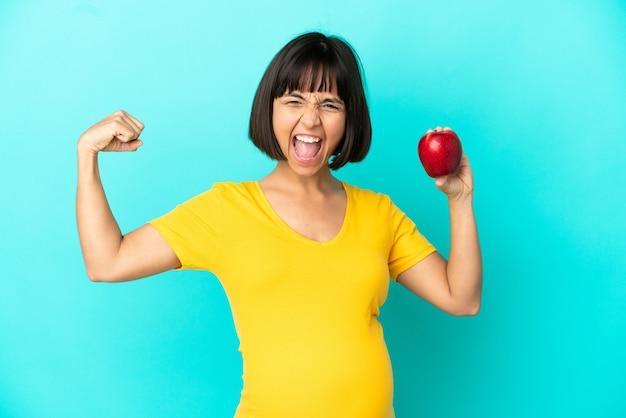 Беременная женщина, держащая яблоко, изолированное на синей стене, делает сильный жест