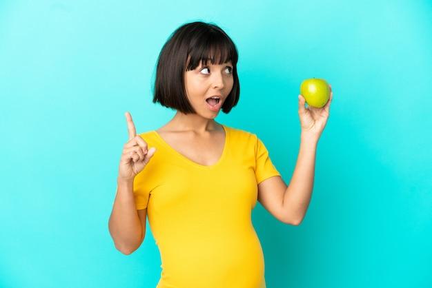 Беременная женщина держит яблоко, изолированное на синей стене, думая, что идея указывает пальцем вверх