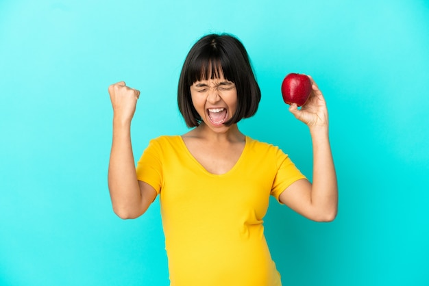 Pregnant woman holding an apple isolated on blue background celebrating a victory