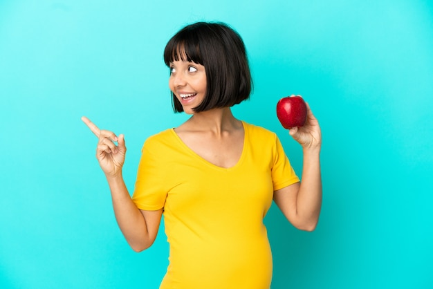 Pregnant woman holding an apple isolated on blue background intending to realizes the solution while lifting a finger up