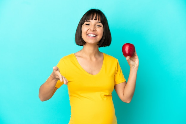 Pregnant woman holding an apple isolated on blue background shaking hands for closing a good deal