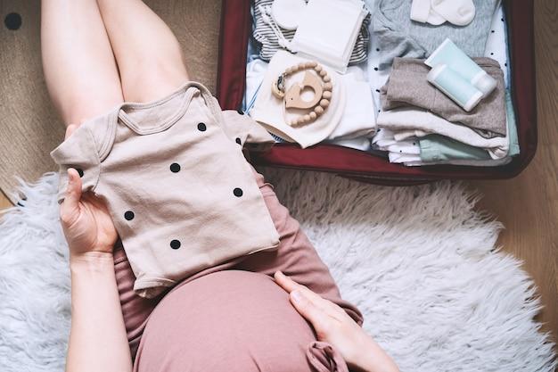 Беременная женщина держит детское боди и упаковывает сумку родильного дома матери во время беременности