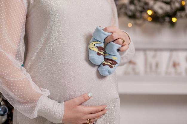 Беременная женщина, держащая детские пинетки. живот с пинетками крупным планом.