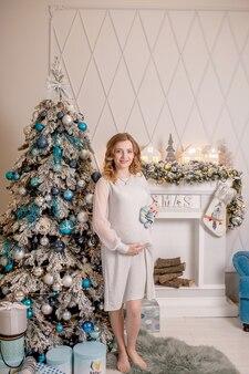 Беременная женщина, держащая детские пинетки живот с пинетками крупным планом