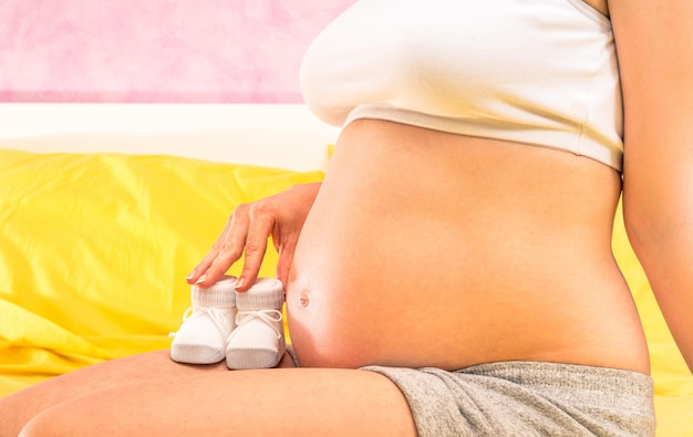 Pregnant woman holding baby booties shoe at the belly sitting in her sleeping room at home