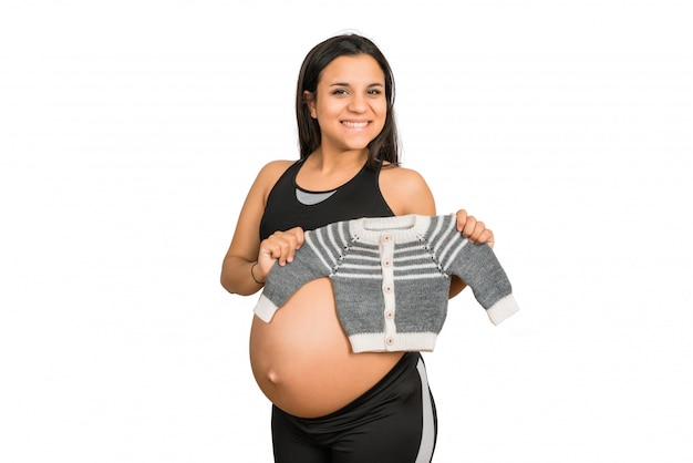 Pregnant woman holding baby clothes.