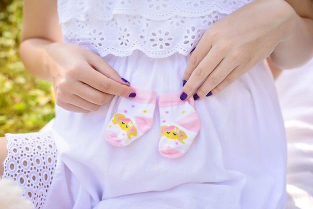 Pregnant woman holding baby socks near the tummy