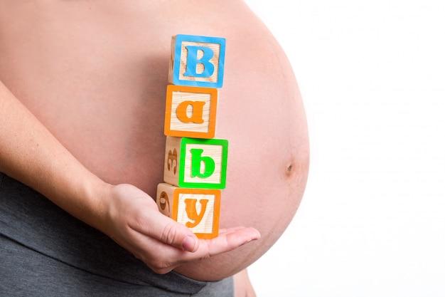 コピースペースで赤ちゃんの単語を保持している妊娠中の女性