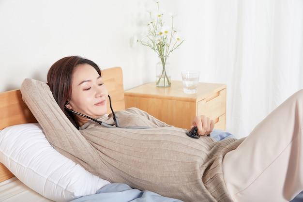 携帯電話を持って音楽を聴いている妊婦