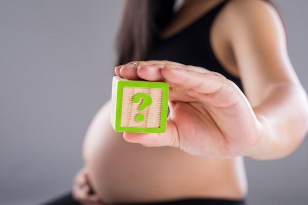 Беременная женщина, держащая древесину куба с вопросительным знаком для ребенка. дети мужского или женского пола.
