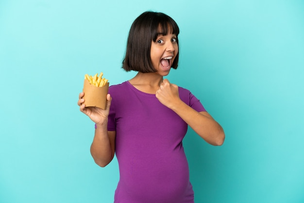 Pregnant woman holding fried chips over isolated background celebrating a victory