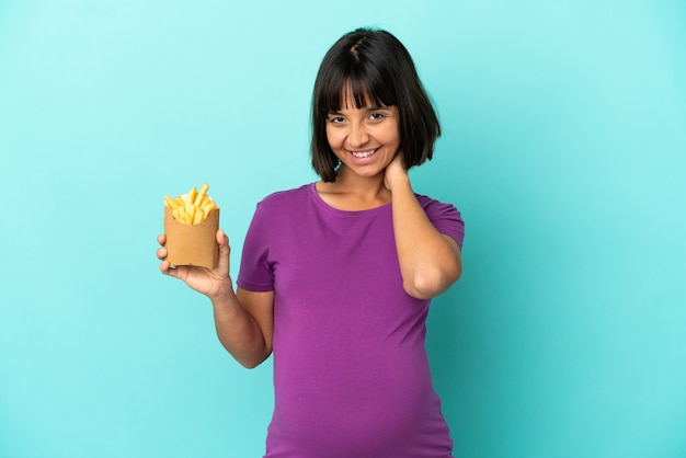 Pregnant woman holding fried chips over isolated background laughing