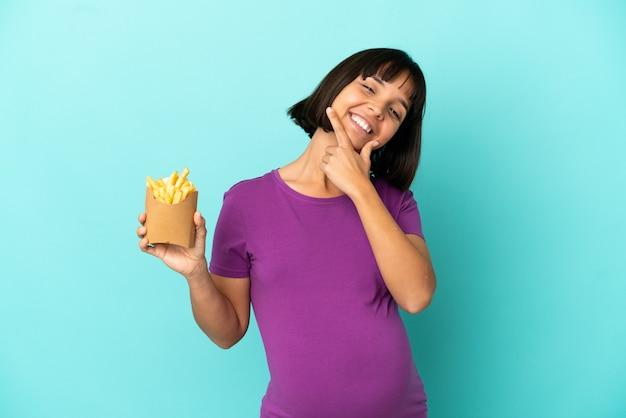 고립 된 배경 위에 튀긴 칩을 들고 행복 하 고 웃는 임신한 여자