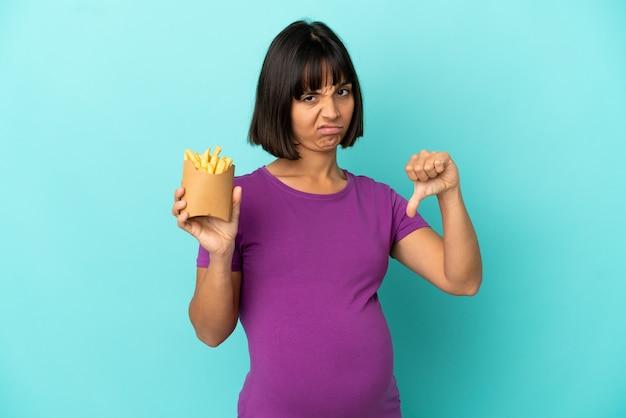 부정적인 표정으로 엄지손가락을 아래로 보여주는 고립 된 배경 위에 튀긴 칩을 들고 임신한 여자
