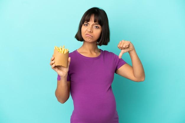 부정적인 표현으로 아래로 엄지 손가락을 보여주는 고립 된 벽 위에 튀긴 칩을 들고 임신 한 여자