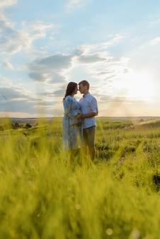 일몰에 분야에서 산책하는 동안 그녀의 남편과 손을 잡고 임신 한 여자. 행복한 가족과 신생아.