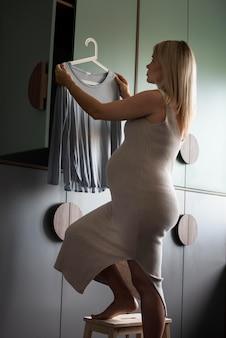 Беременная женщина, держащая вешалку с рубашкой