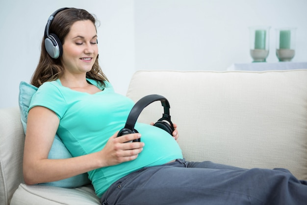 Pregnant woman holding headphone on belly on couch