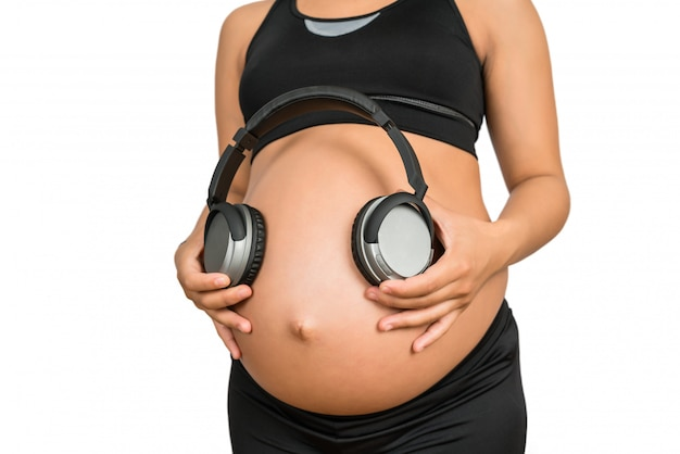 Pregnant woman holding headphones on belly.
