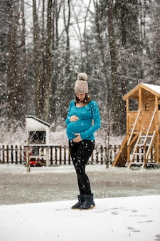 Pregnant woman holding her belly standing outside in winter hat and blue sweater under snowfall in rural area