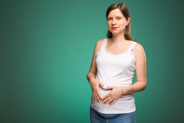 아기가 태어날 것을 기대하는 그녀의 배꼽에 심장 기호에 그녀의 손을 잡고 임신한 여자