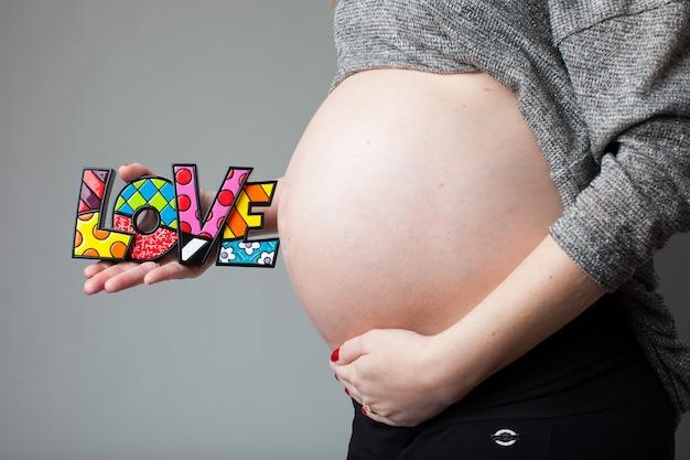 사랑의 단어를 들고 임신한 여자