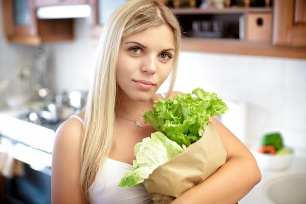 Беременная женщина, держащая бумажный пакет с листьями салата