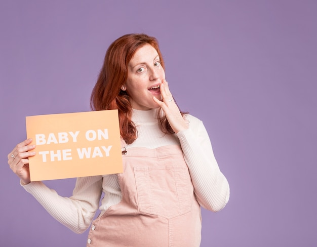 Pregnant woman holding paper with baby on the way message