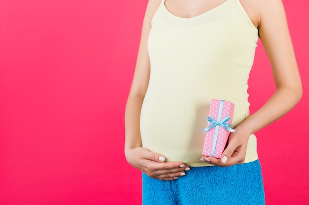Pregnant woman in  holding pink spotted gift box