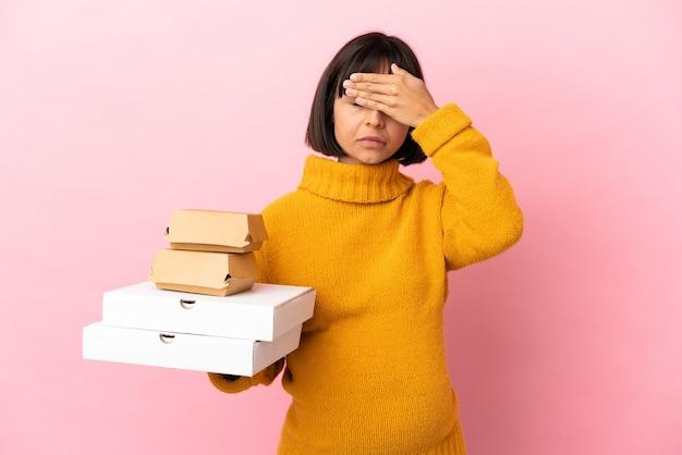 분홍색 배경에 격리된 피자와 햄버거를 들고 손으로 눈을 가리고 있는 임산부. 뭔가 보고 싶지 않아