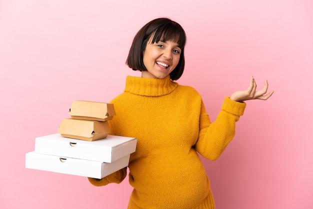 ピンクの背景に分離されたピザやハンバーガーを持っている妊婦は、来て招待するために手を横に伸ばします