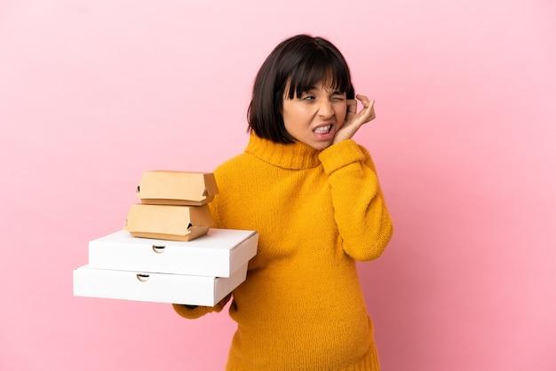 Беременная женщина, держащая пиццу и гамбургеры, изолированные на розовом фоне, разочарована и закрывает уши