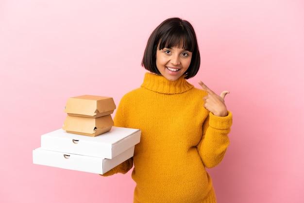 ピンクの背景に分離されたピザやハンバーガーを持っている妊婦が親指を立てるジェスチャーを与える