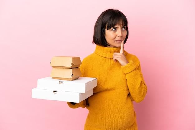 見上げている間疑いを持っているピンクの背景に分離されたピザやハンバーガーを保持している妊婦