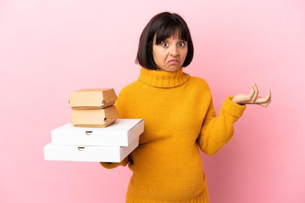 ピンクの背景で隔離のピザやハンバーガーを保持している妊娠中の女性が手を上げながら疑問を持っている