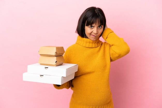 疑いを持っているピンクの背景に分離されたピザやハンバーガーを保持している妊婦 Premium写真