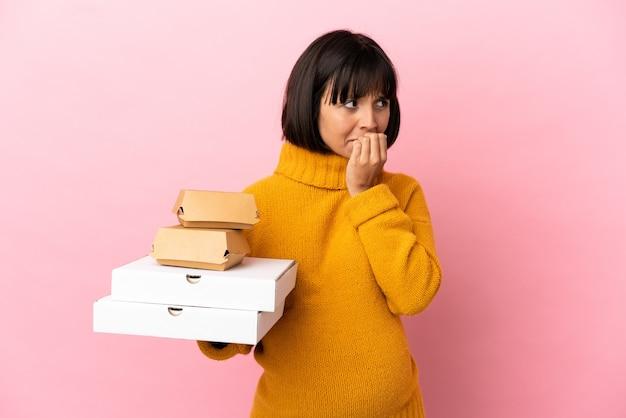 Беременная женщина, держащая пиццу и гамбургеры, изолированные на розовом фоне, сомневаясь