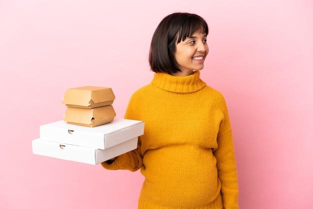 側面を見てピンクの背景に分離されたピザやハンバーガーを保持している妊婦